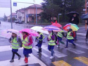 Bambini sotto la pioggia a scuola col piedibus